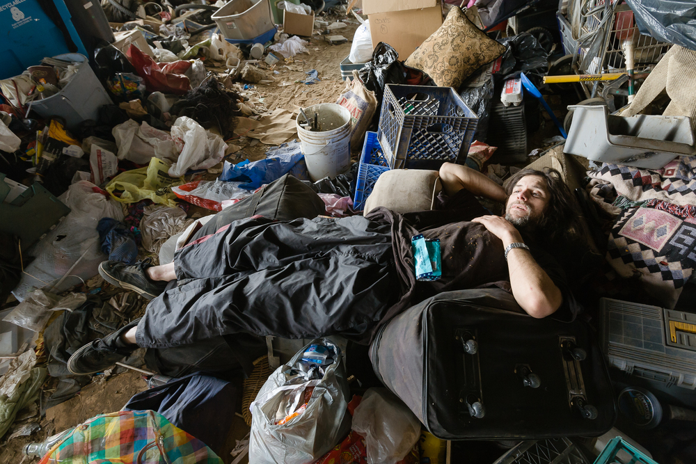 After a hard day of scrapping, Steve, lays down in a rat's nest of detritus back at camp to ponder his situation. New to the camp he lives in a make shift tent amongst a pile of garbage.