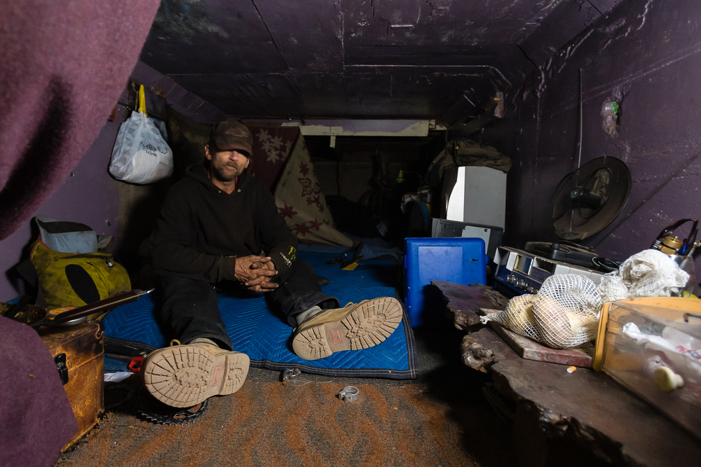 Inside a 4'x4'x20' crawl space, Steve keeps his area very tidy. He says today was a messy day for him. His space is wired with electricity, powering his light and radio. The space rattles continuously as cars pass by overhead.