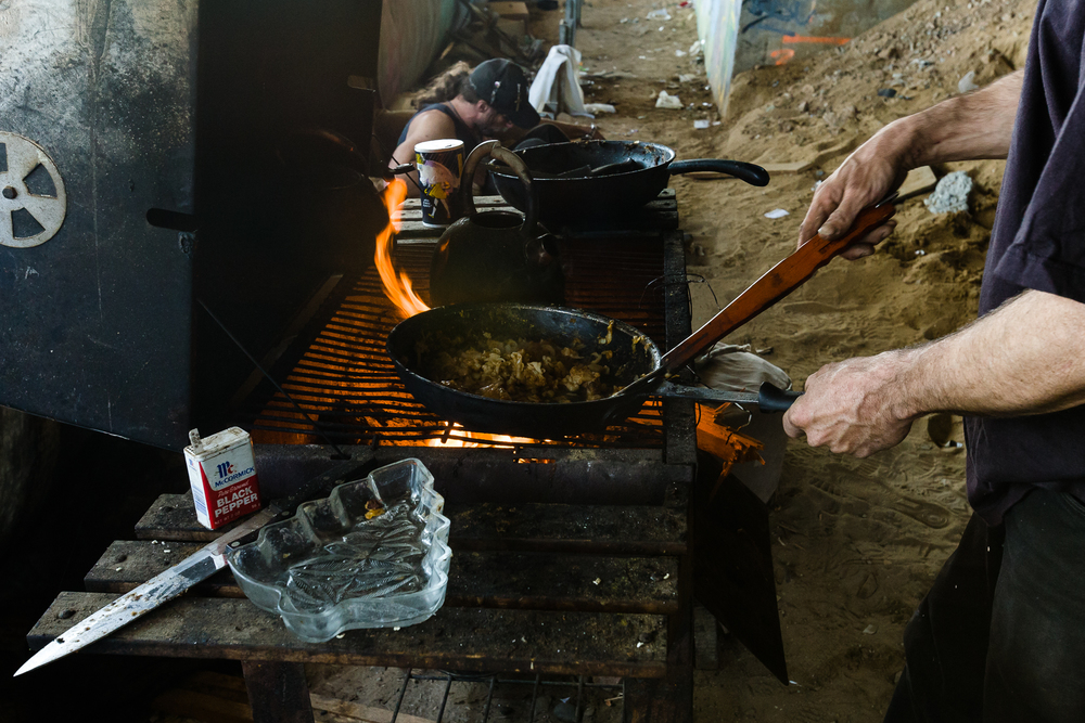 A wood burning BBQ is used to heat the previous night's leftovers, and water for coffee. The camp inhabitants all join together for breakfast and coffee before heading out for a long day of scrapping.