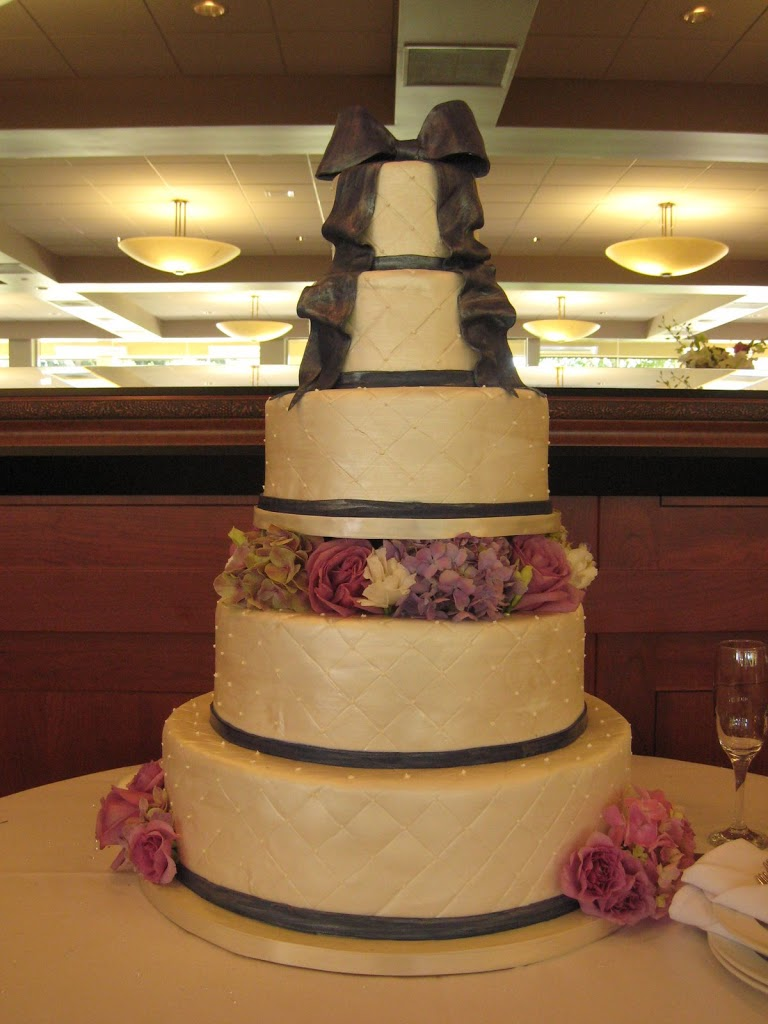 This large wedding cake was detailed in a quilted pattern in fondant with painted navy bands and bow. The quilted look does look best in fondant.