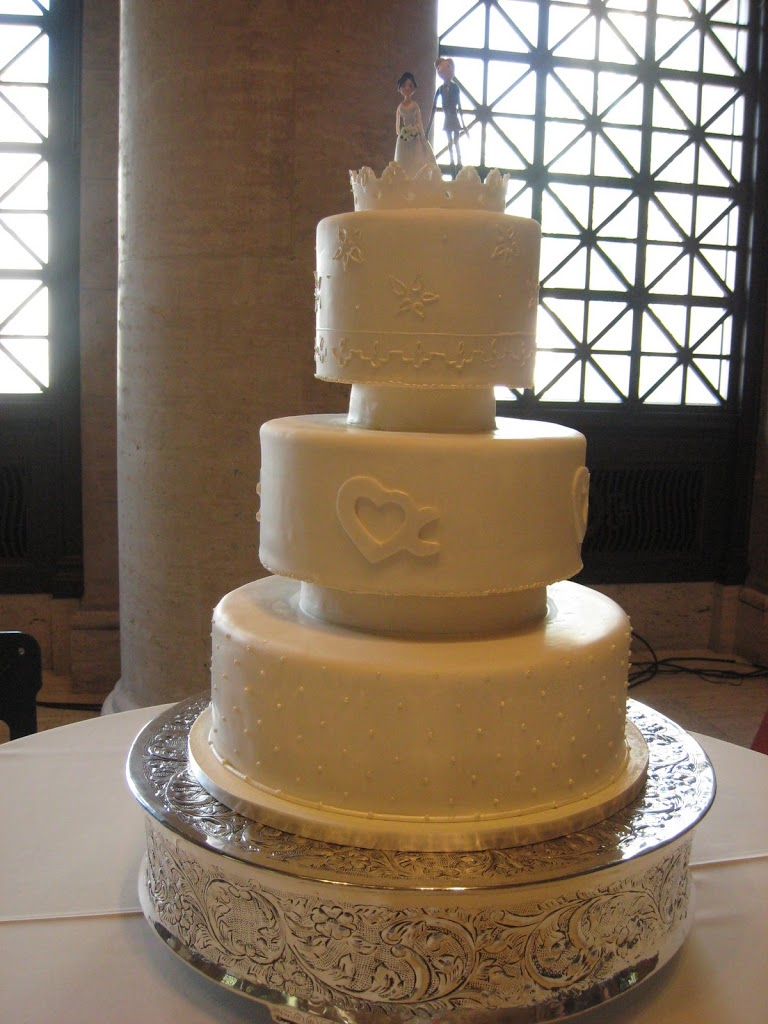 This simple and clean lined cake was for a grand wedding at the Asian Art Museum in San Francisco. The heart shaped logo on the second tier was their monogram as the symbol has an X and C (the couples initials) within the design.The figurine topper was hand made by the bride. They were very cute.