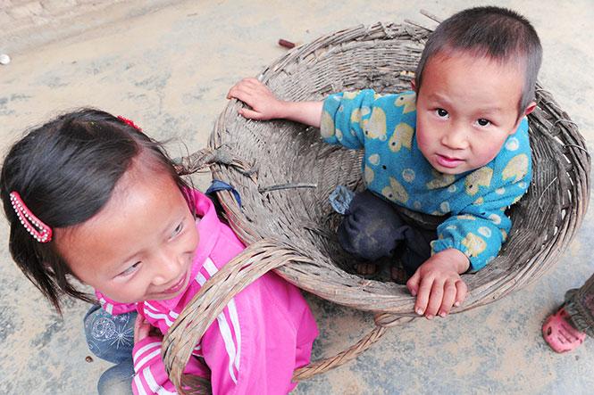 陈船放学回家,爷爷奶奶上山干活去了,弟弟一个人在地上玩耍。她把弟弟抱进一个背篼,背着他玩。.jpg