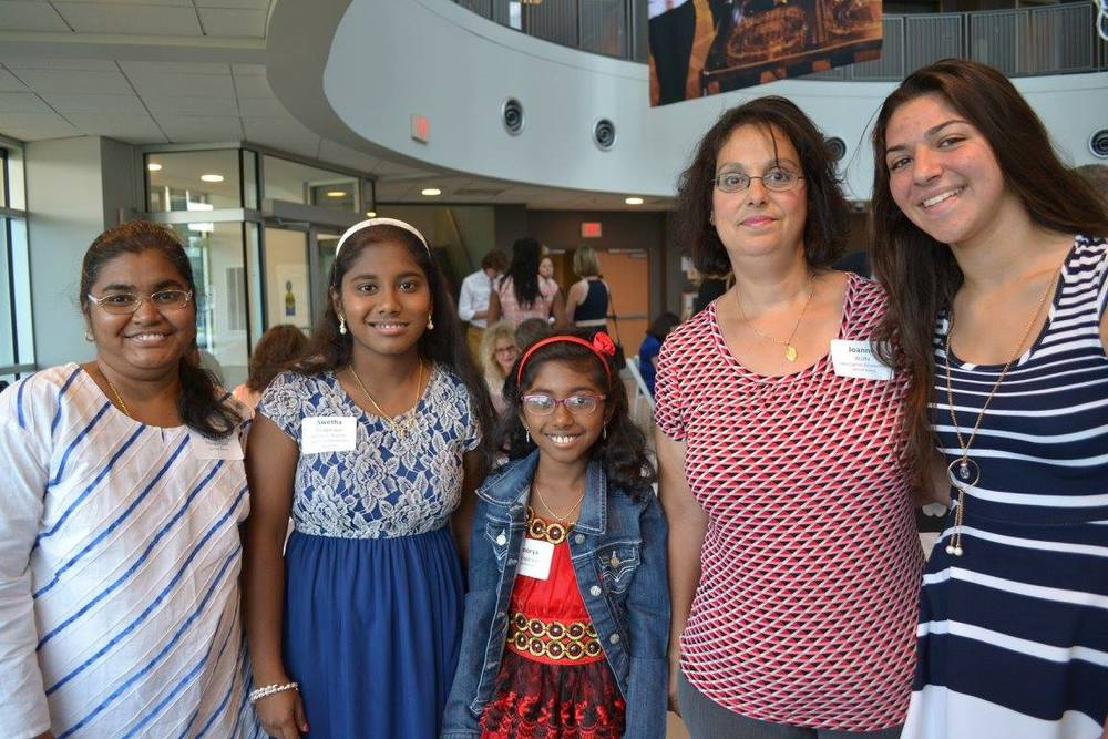Swetha, second from left, and Sabrina (right) with their supportive family members.