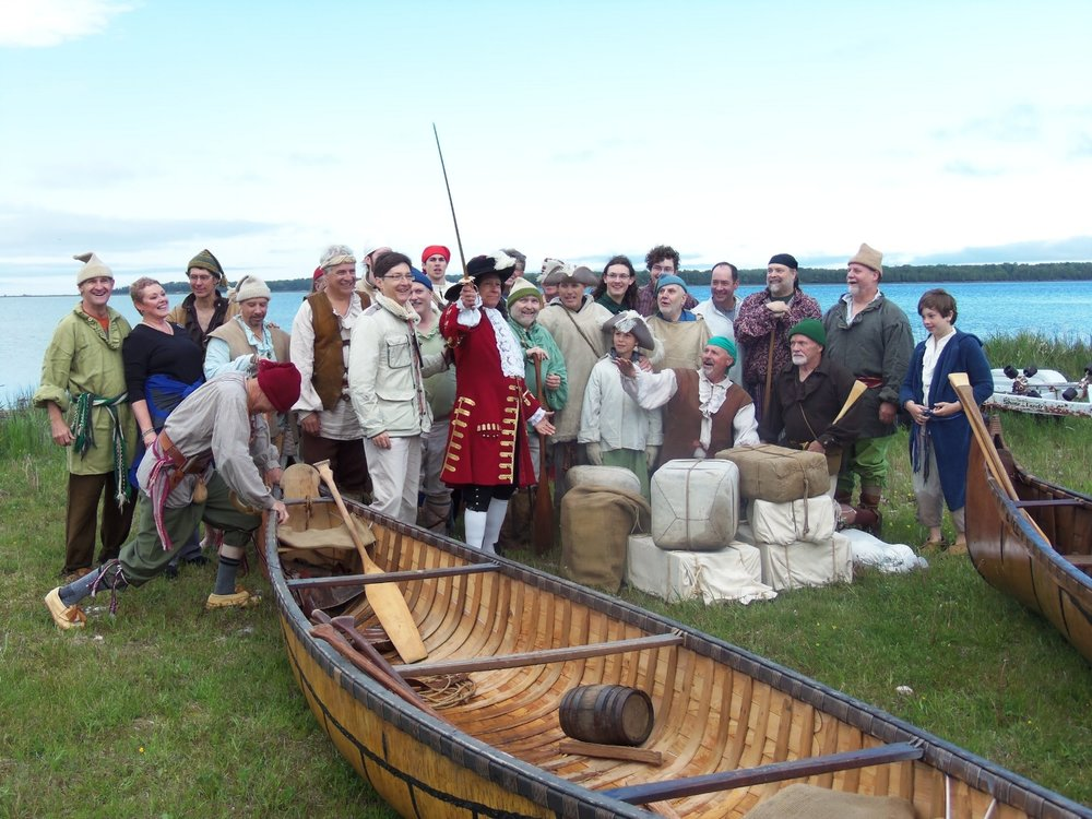 Reid Lewis, reprising his role as the Sieur de La Salle, brandishes a sword on the shore of Lake Michigan in June 2013. He is surrounded by fellow 20th century voyageurs and their children and by French officials. The author is standing at far left.