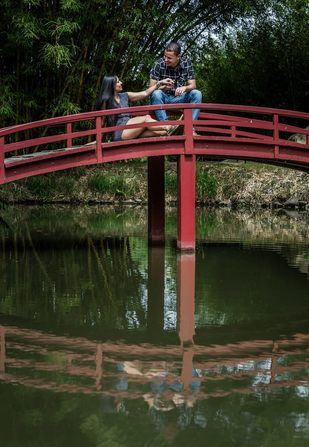 Engagement pictures of couple sitting on quant red bride in botanical garden in Costa Rica.