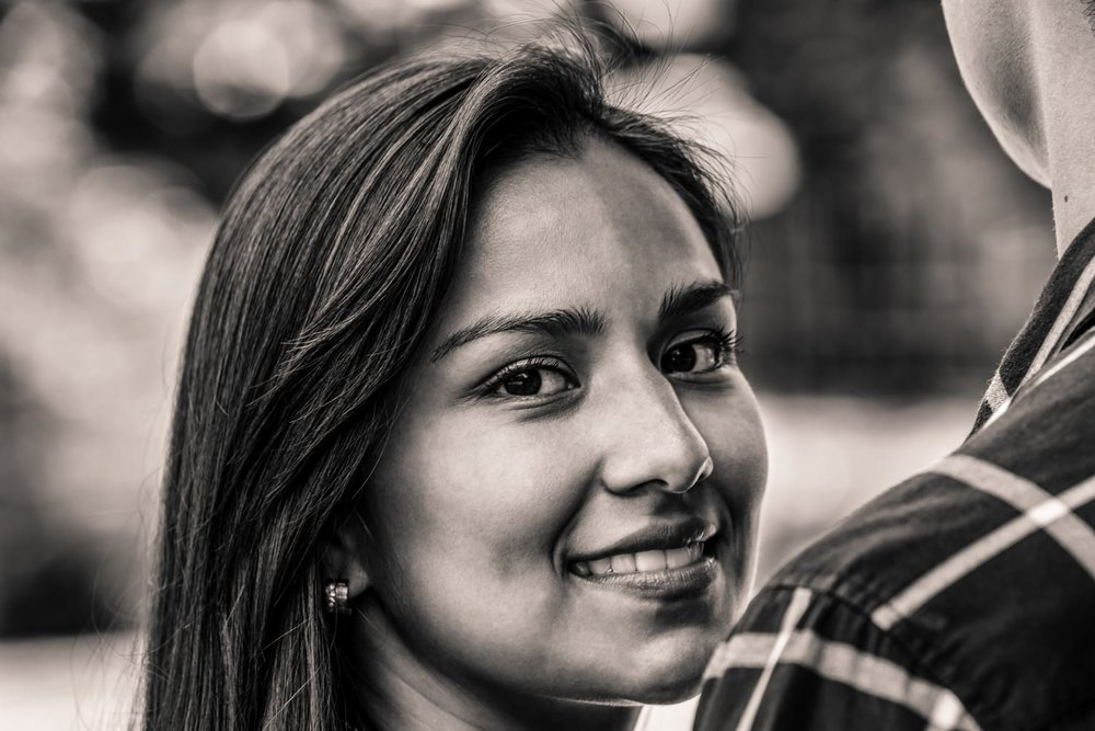 Black and white photo of woman looking over fiancé's shoulder for engagement session.