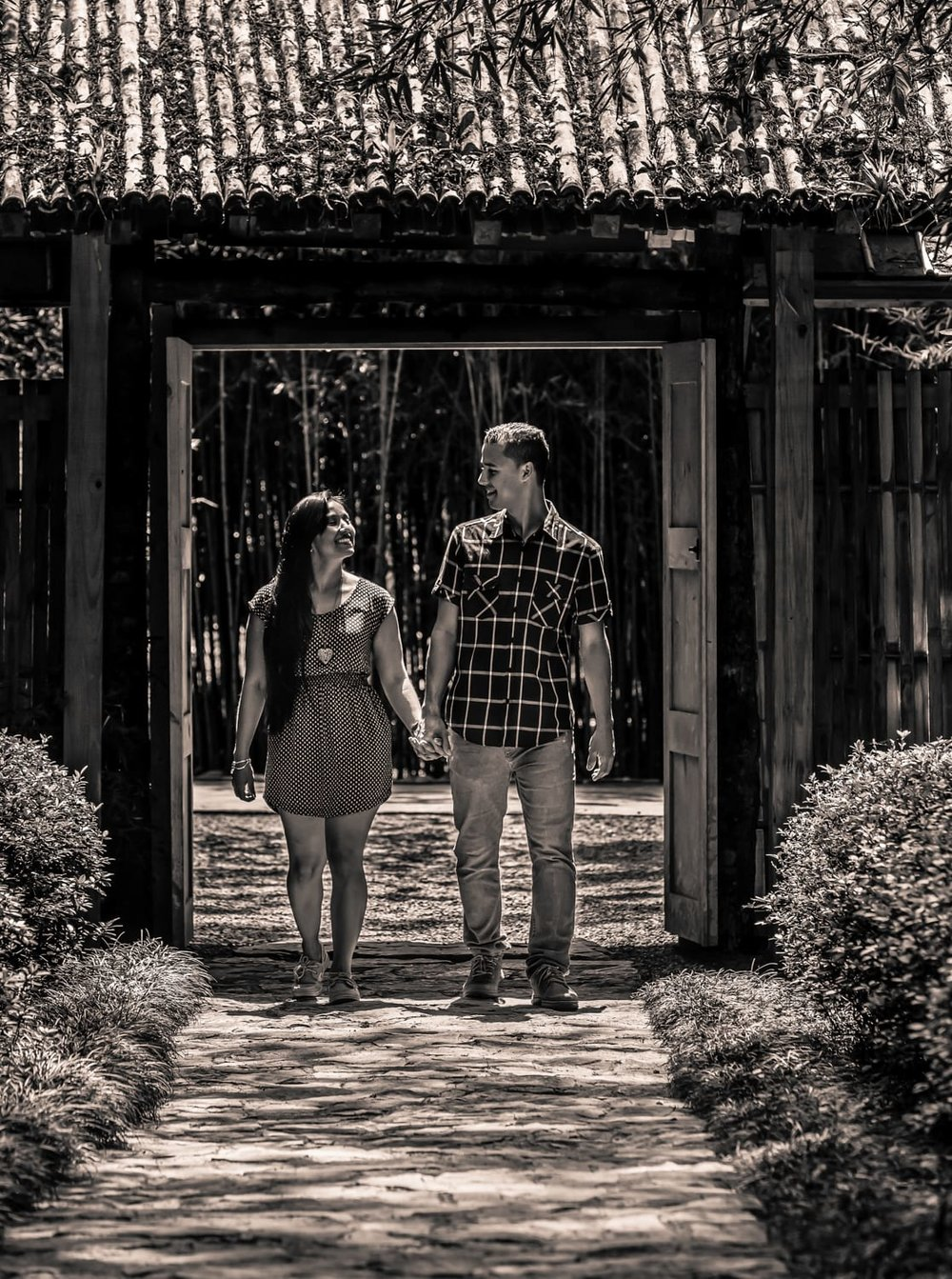 Engagement photo of couple holding hands in botanical garden and walking on stone path.