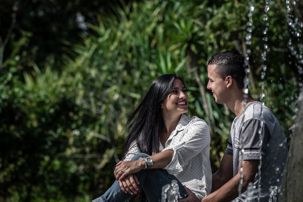 Engagement photos of couple sitting by water fountain in botanical garden in Costa Rica.