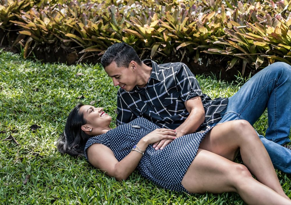 Couple laying in grass at Costa Rica botanical garden for engagement session.