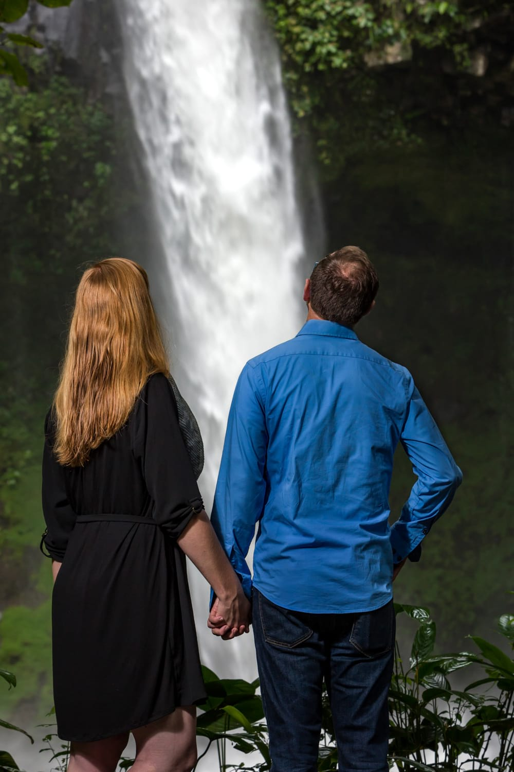 Engaged couple holding hands in front of La Fortuna Waterfall in