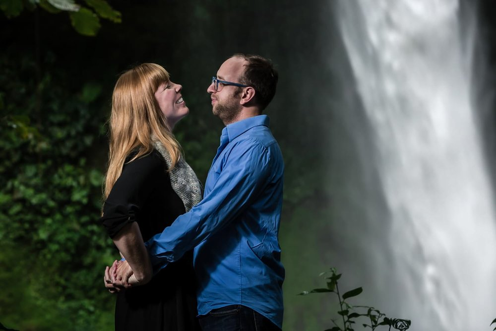 Lovers who just got engaged in Costa Rica stand in front of waterfall with arms intertwined.