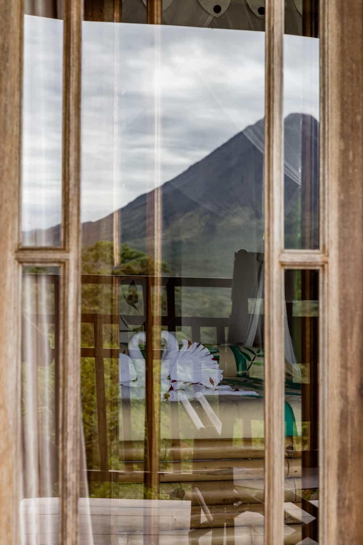Image of honeymoon suite canopy bed taken through balcony window.