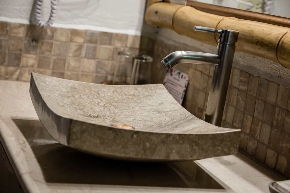 Rectangular stone sink  on stone counter in honeymoon suite bathroom.