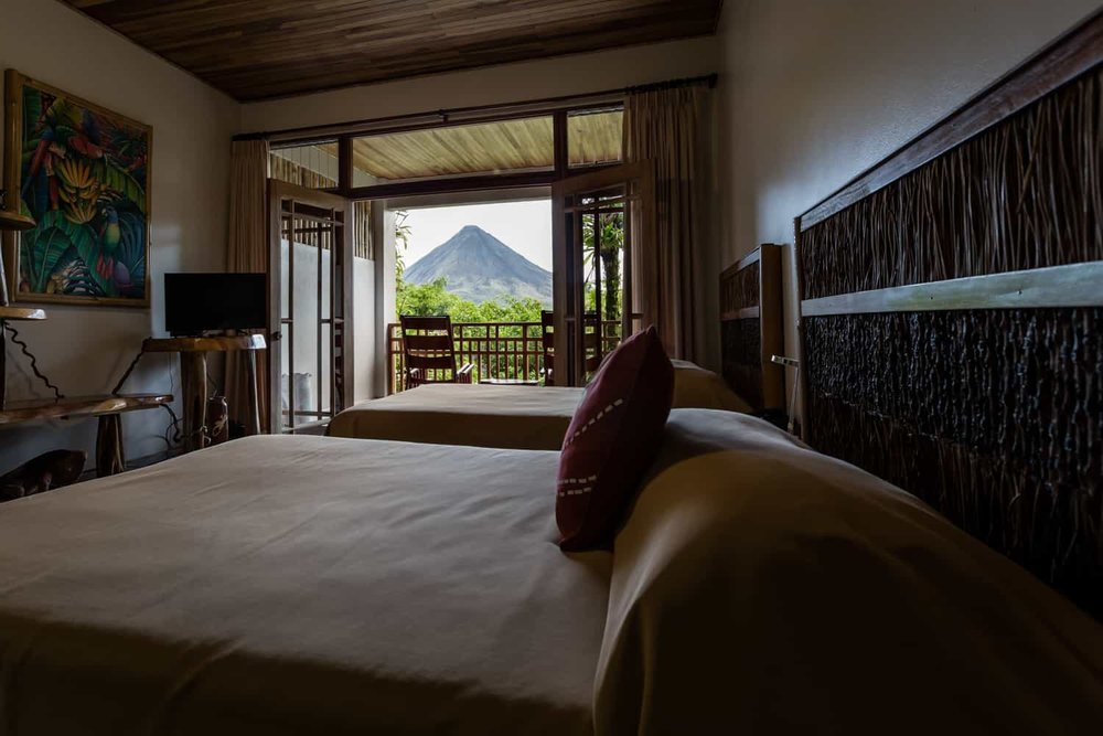 View of Arenal Volcano from beds in room for wedding guests.