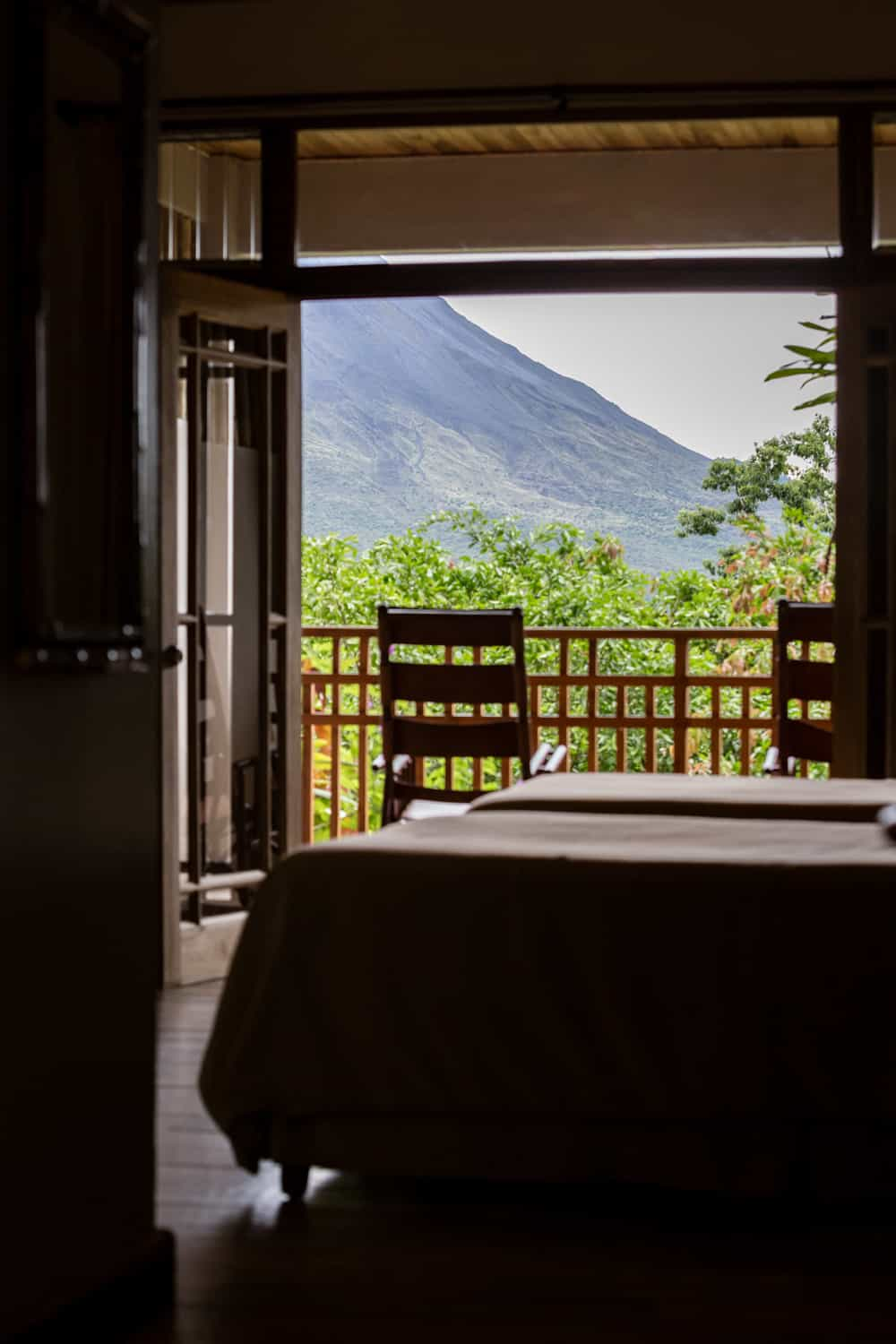 View of balcony overlooking rainforest and Arenal Volcano.