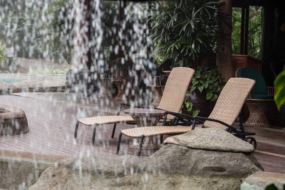 Image of lounge chairs on deck for wedding guests from behind waterfall.
