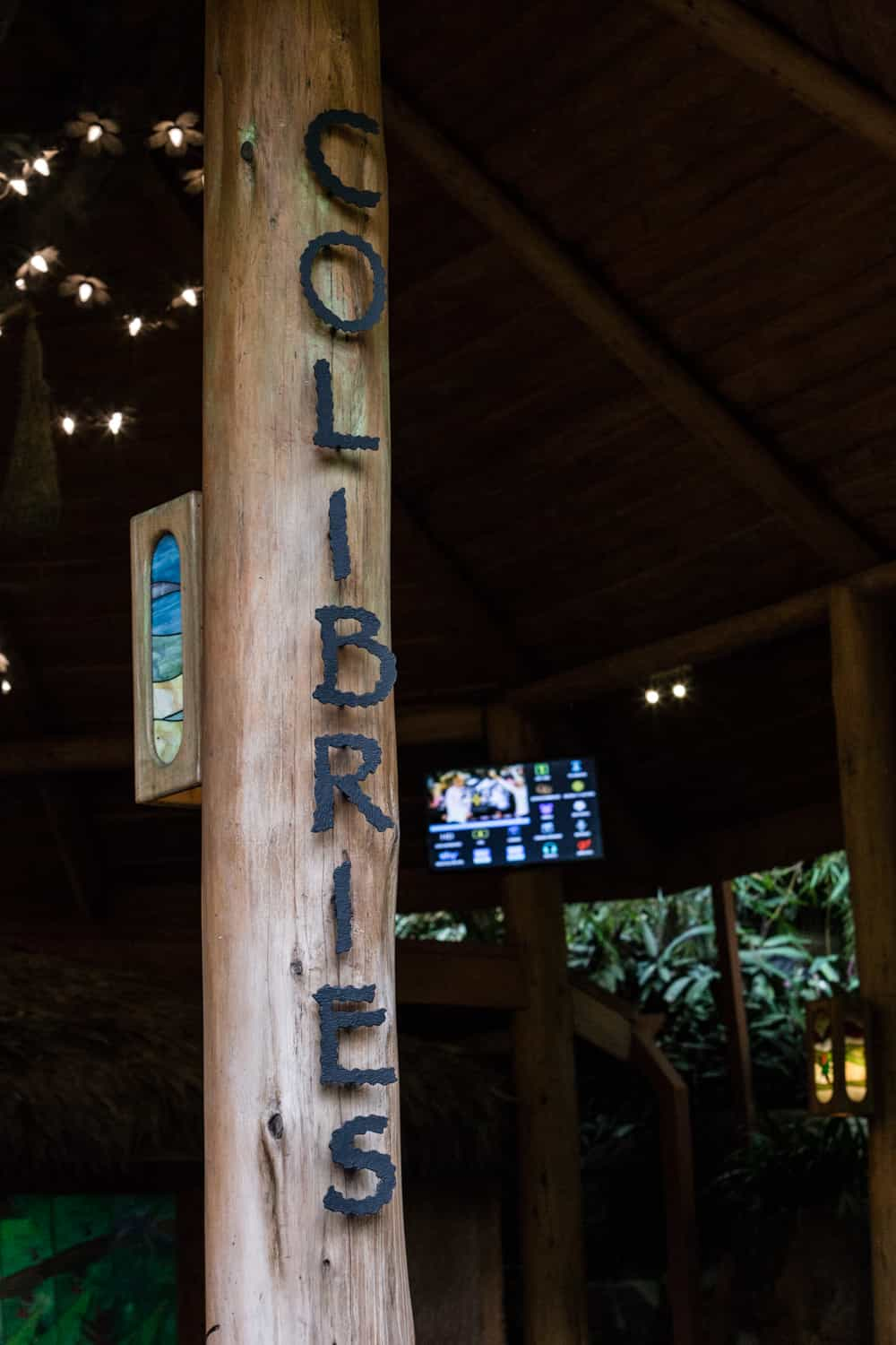 Post at entrance of Colibries wedding reception area with restaurant name.