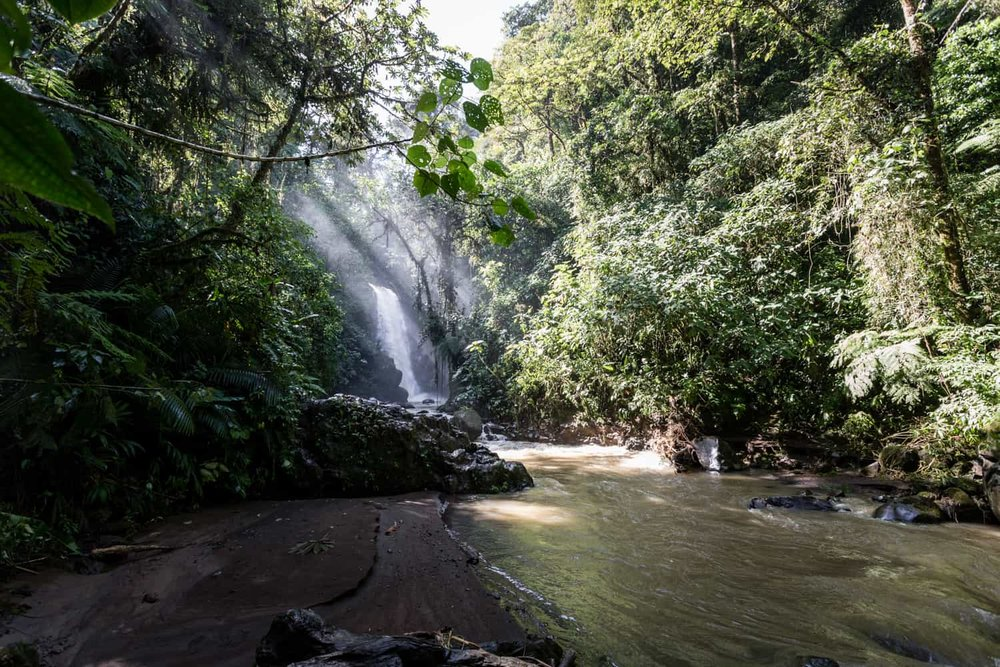 River flows by shore for small weddings near large waterfall in Costa Rica.