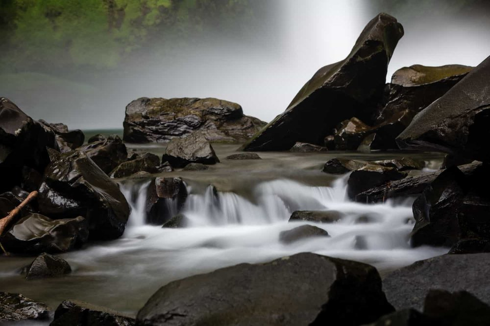 Long exposure photo of river flowing over rocks with base of La Fortuna Waterfall in Background.