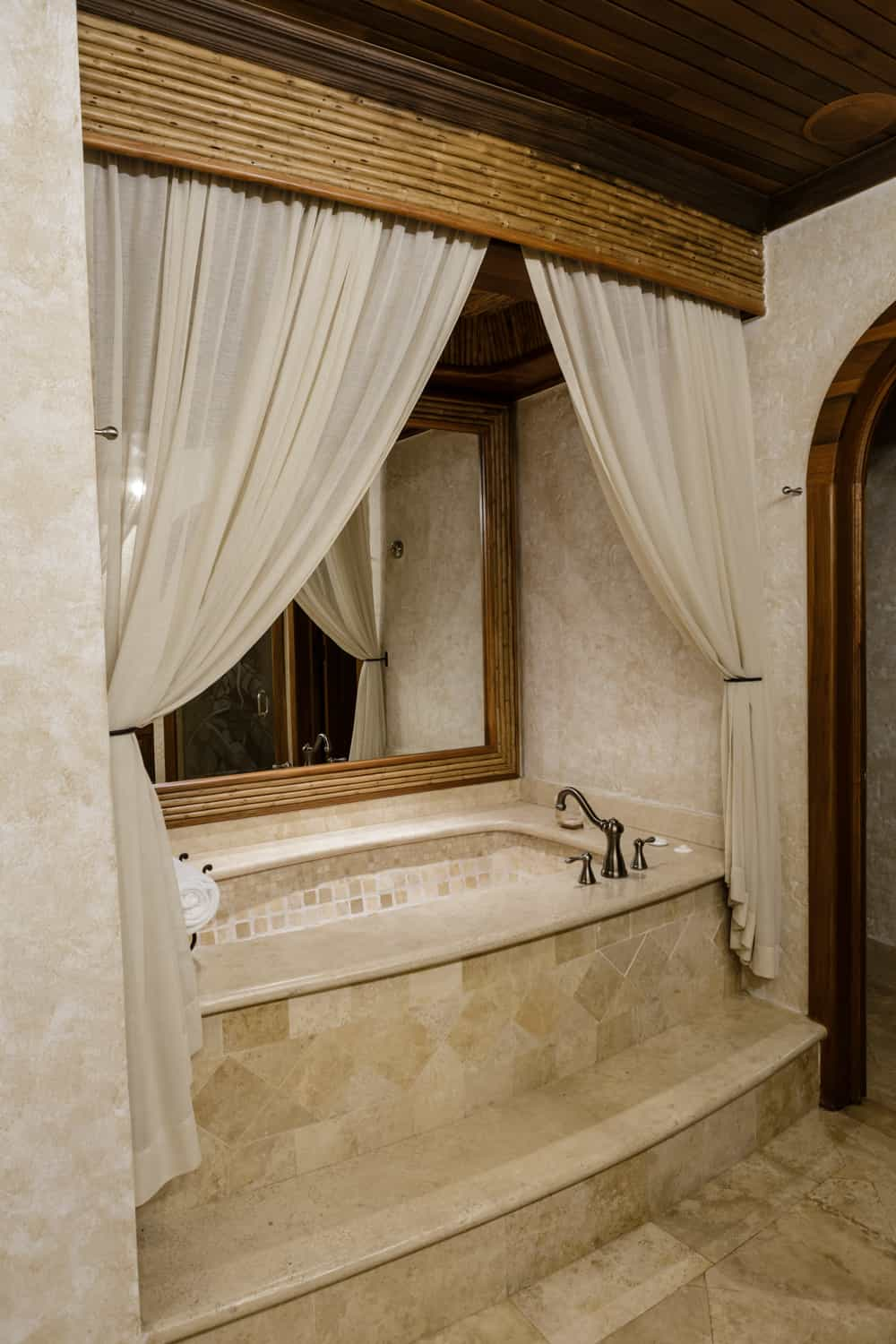 Jacuzzi tub niche in natural stone with curtains.
