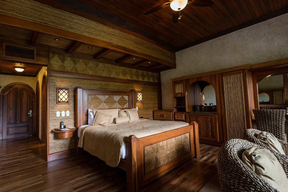 Wood king bed in large honeymoon suite bedroom.