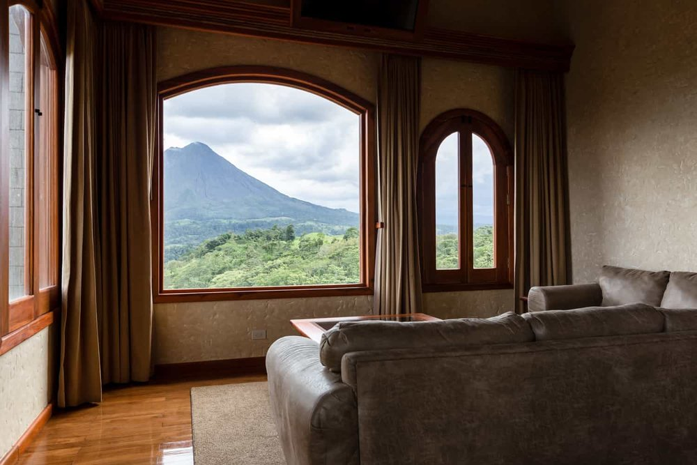 View of Arenal volcano through large window master bedroom.