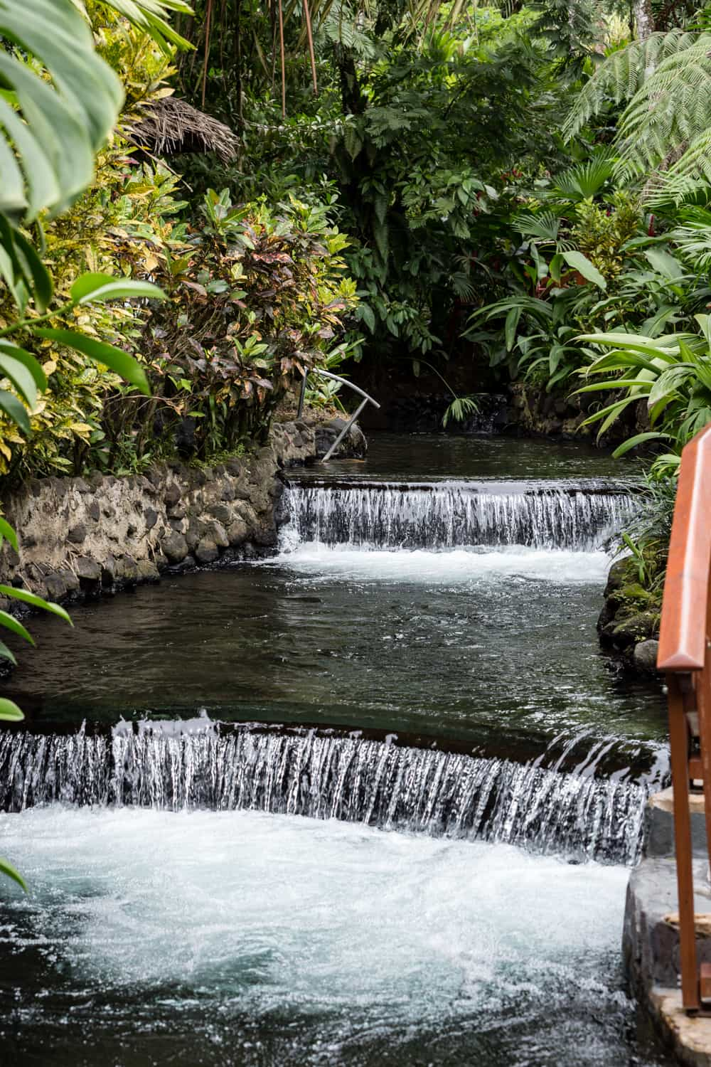 Water from Arenal thermal springs cascades over picturesque waterfalls at Tabacon Resort.