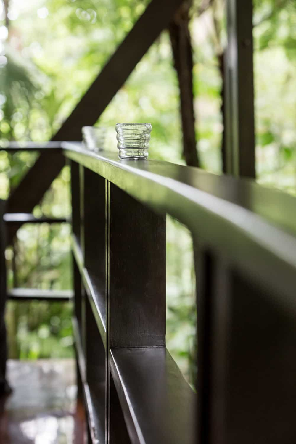 Candles on wood railing in rainforest elopement site.