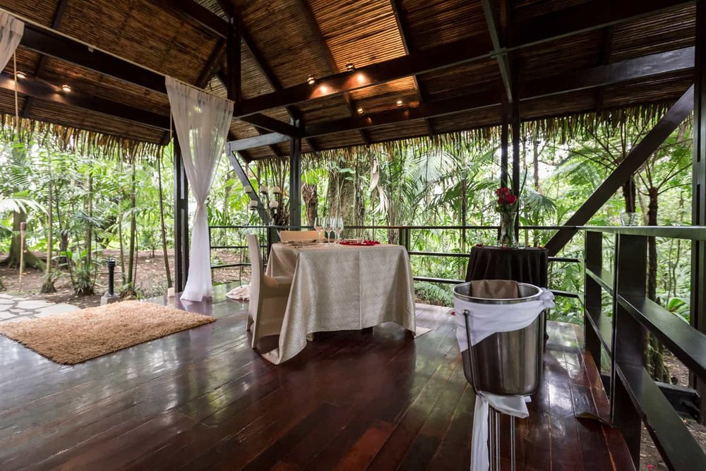 Intimate dining table in bungalow with wood floors in rainforest.