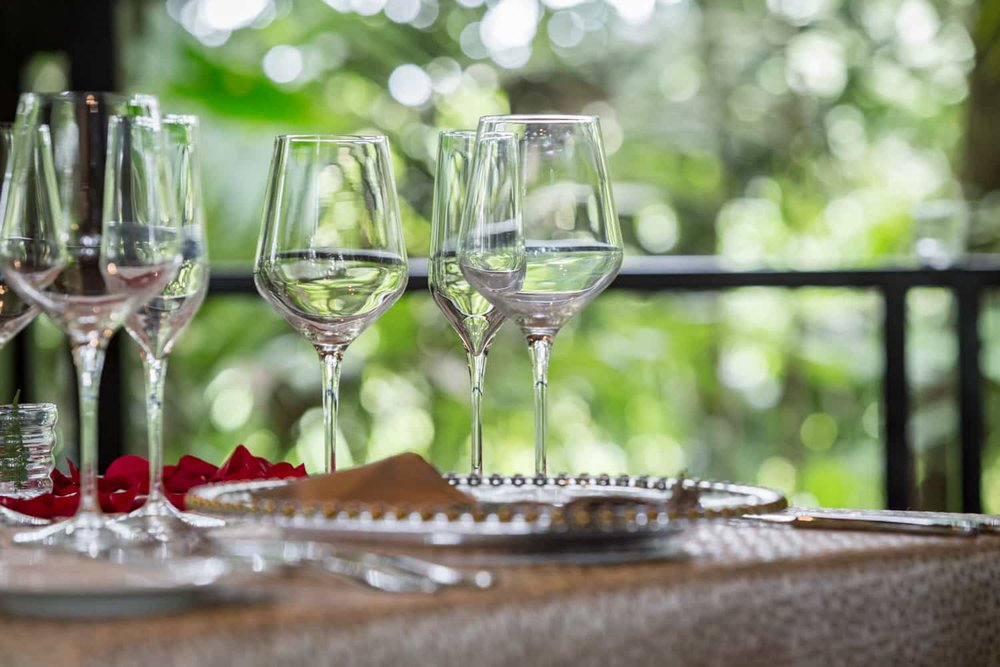 Romantic table setting with rose petals and wine glasses in tropical bungalow.