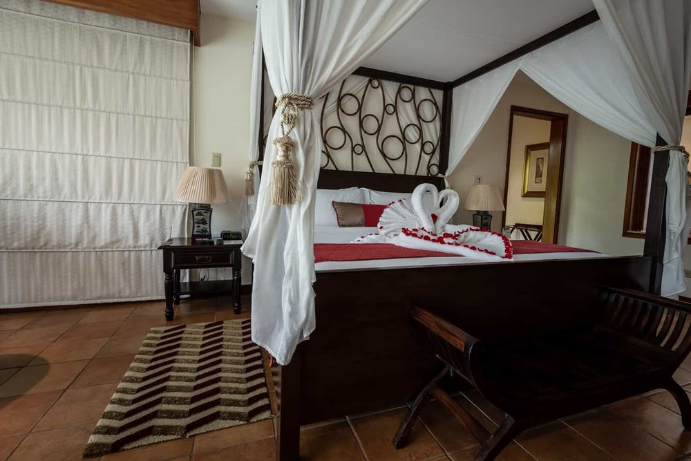 Solid wood honeymoon suite canopy bed with white curtains.