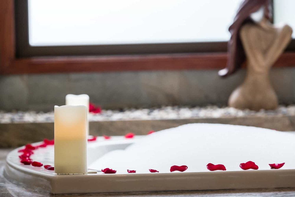 Romantic candles and rose petals on edge of hot tub.