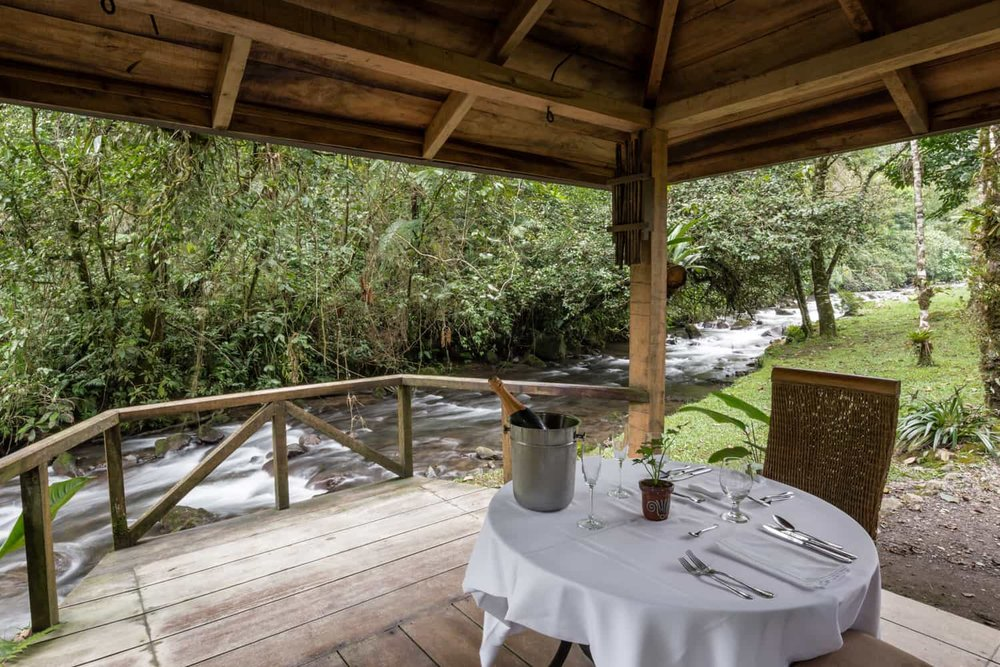 River flowing past romantic dinner table in El Silencio lodge gazebo.