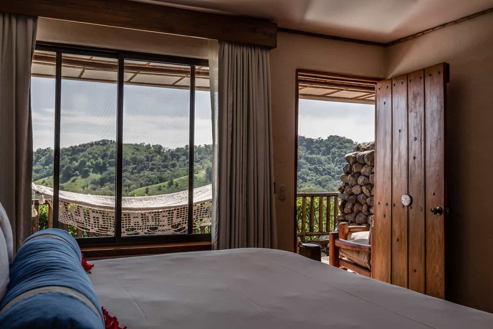 King size bed with view of mountains in deluxe room.