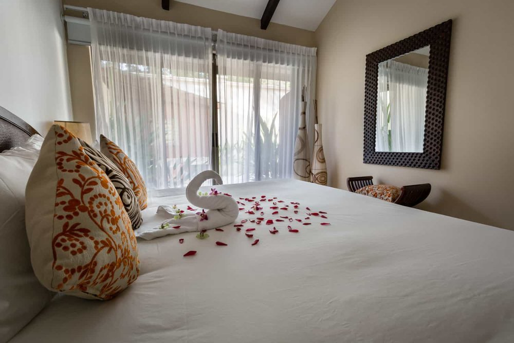 Rose petals on bed in beach front honeymoon suite in Guanacaste.