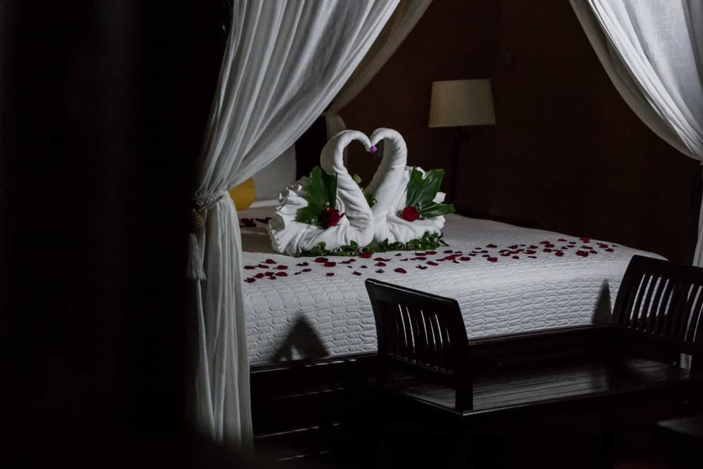 Honeymoon suite bed decorated with red rose petals and swans.
