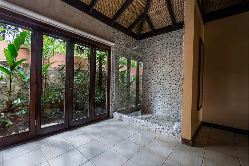 Large bathroom with walk in shower at Rio Celeste Hideaway Hotel.