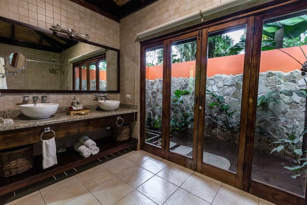 French doors in amazing bathroom lead to outdoor shower in rainforest.