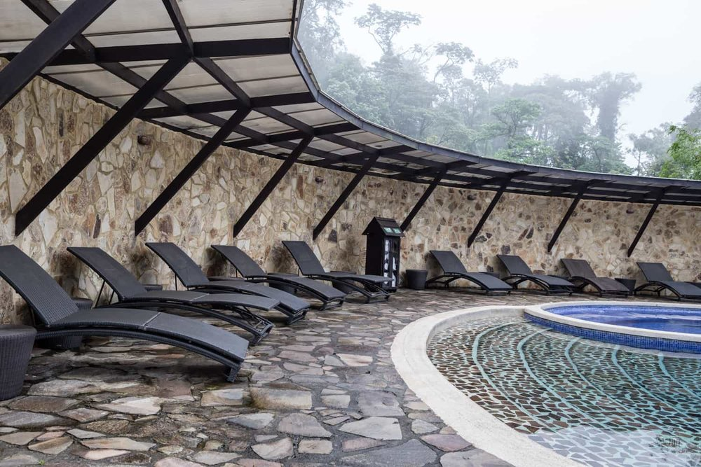 Pool chairs line stone wall for wedding guests at Rio Celeste Hideaway Hotel.