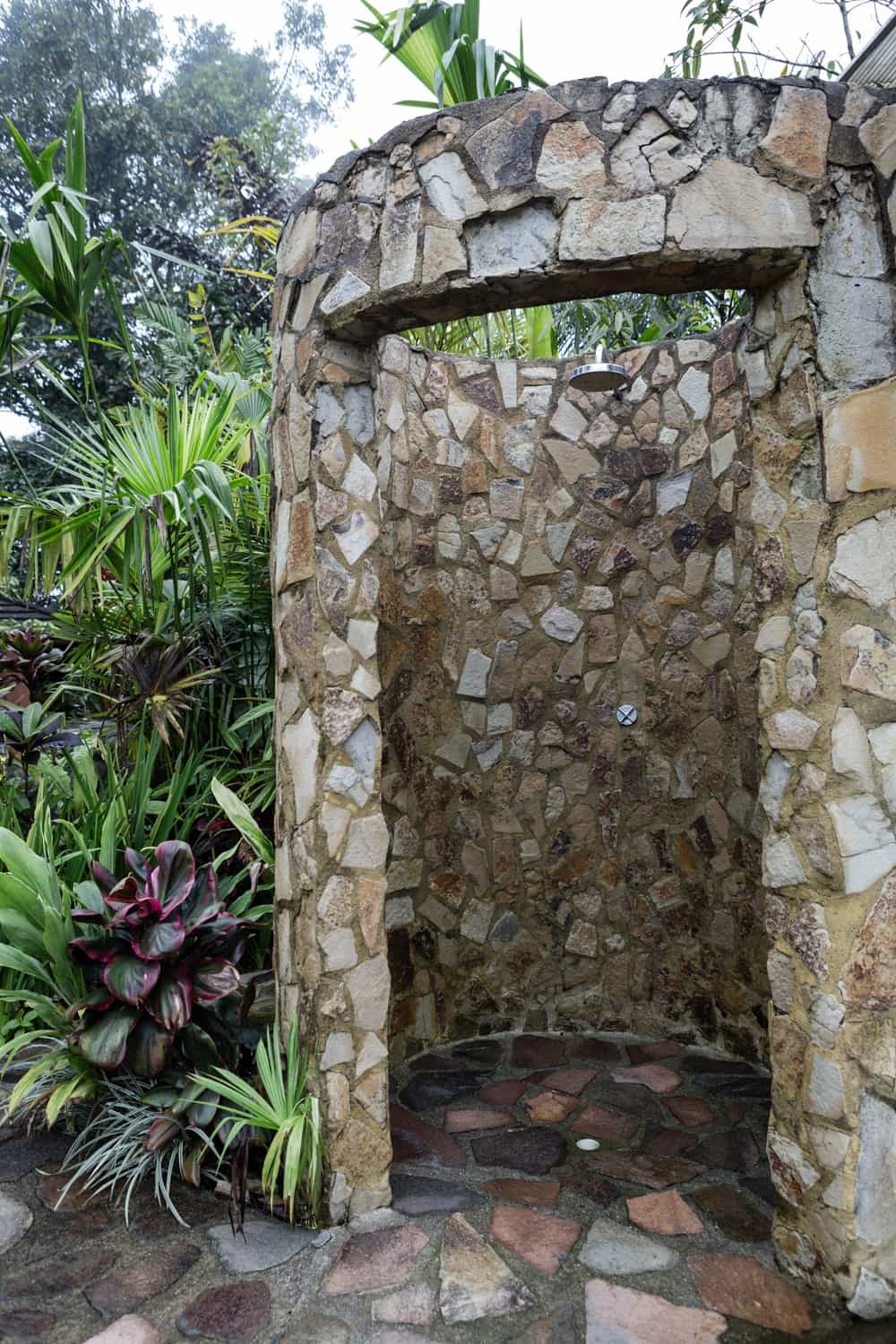 Stone shower by pool next to rainforest.