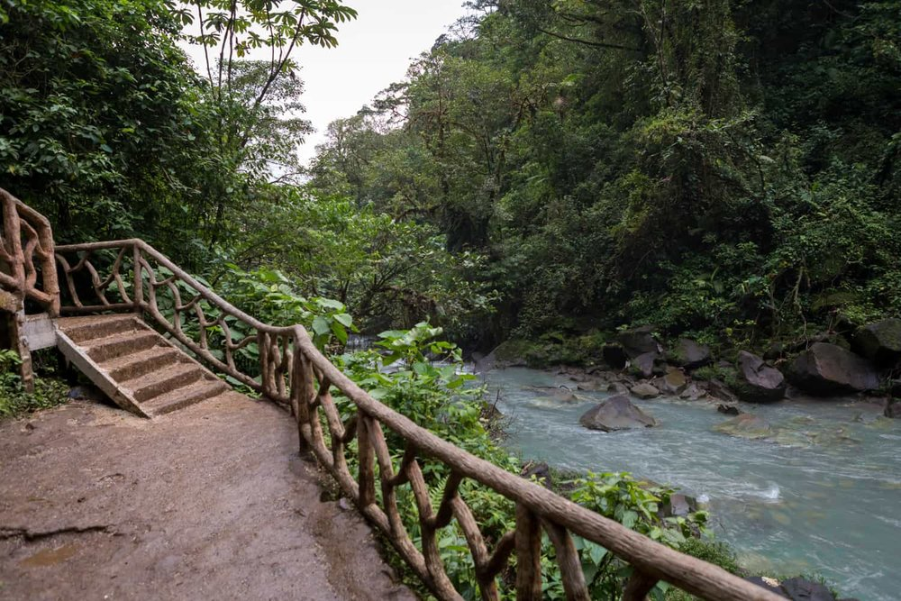 Wedding ceremony terrace next to blue river flowing from Rio Celeste Waterfall.
