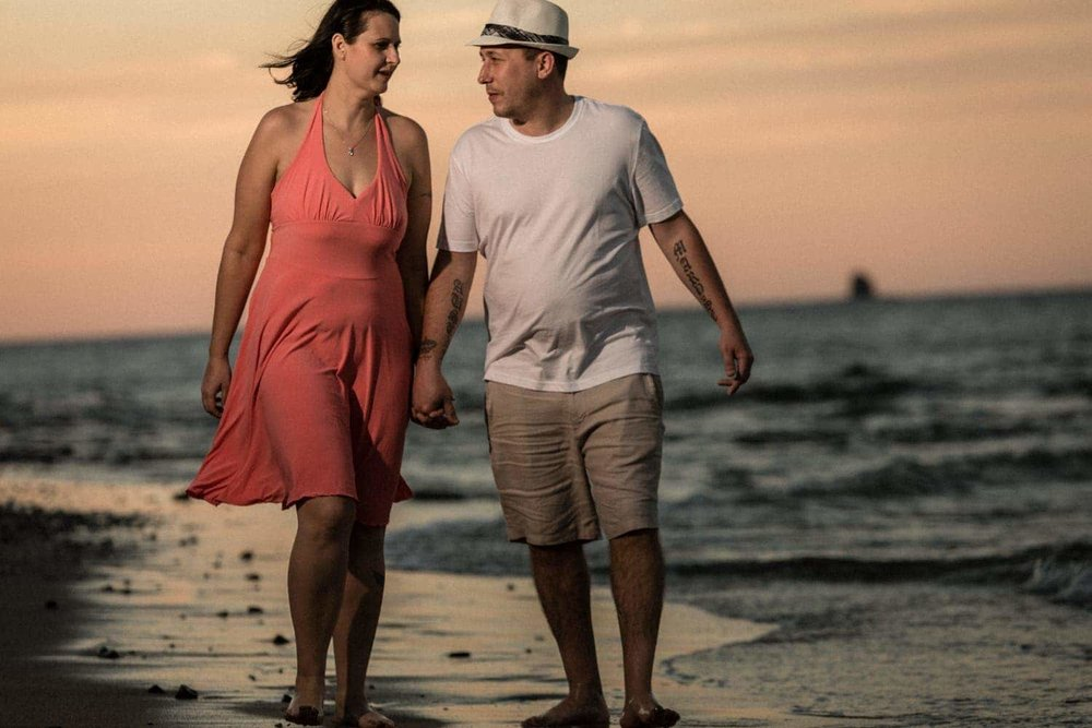 Sunset engagement photo of couple walking beach.