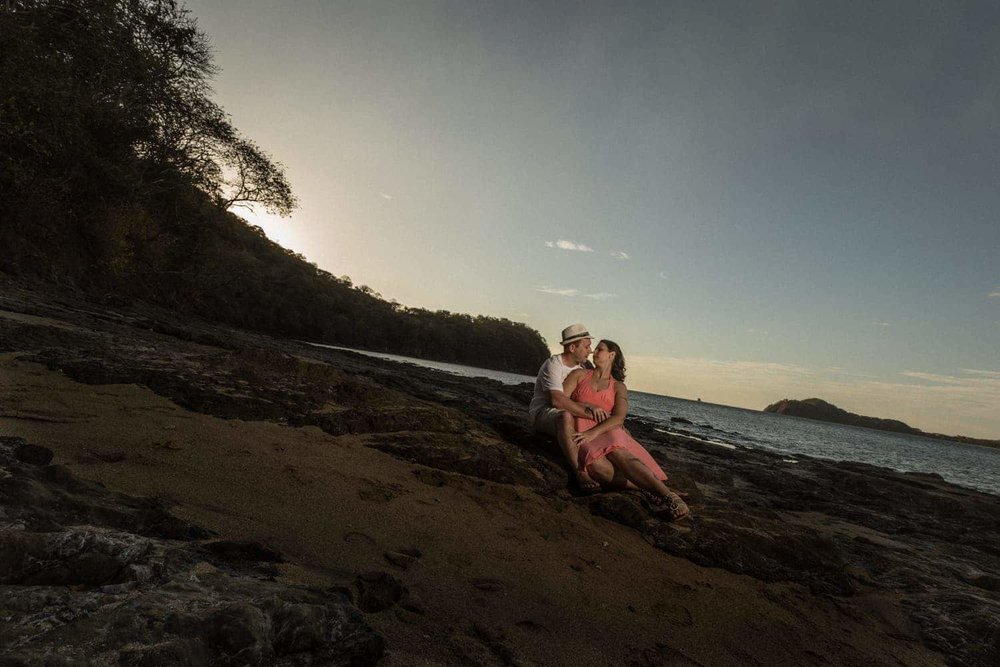 Romantic photo of engaged couple sitting on beach at sunset in Costa Rica.