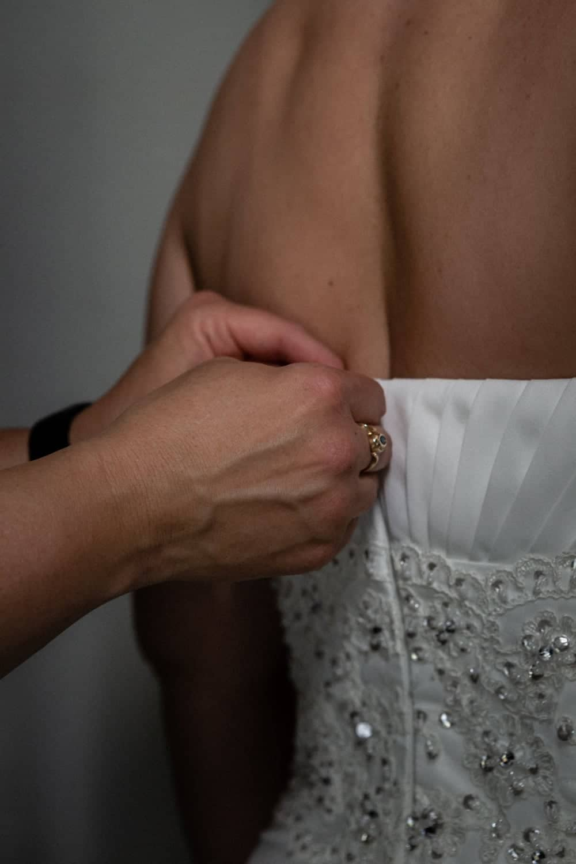 Bridesmaid helping bride put on wedding dress.