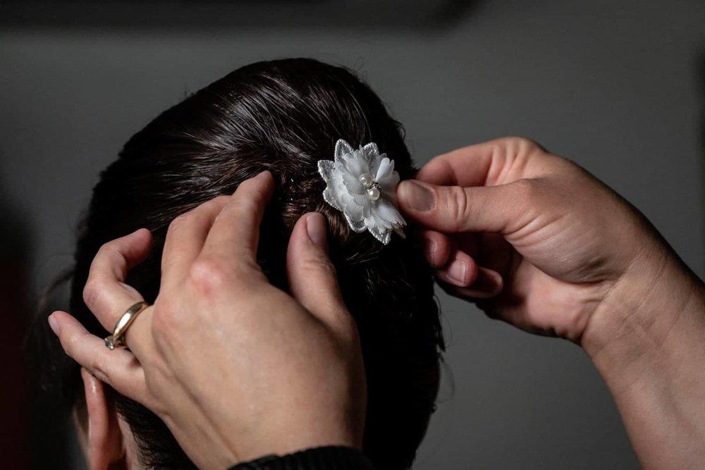 Bridesmaid putting flower in bride's hair.