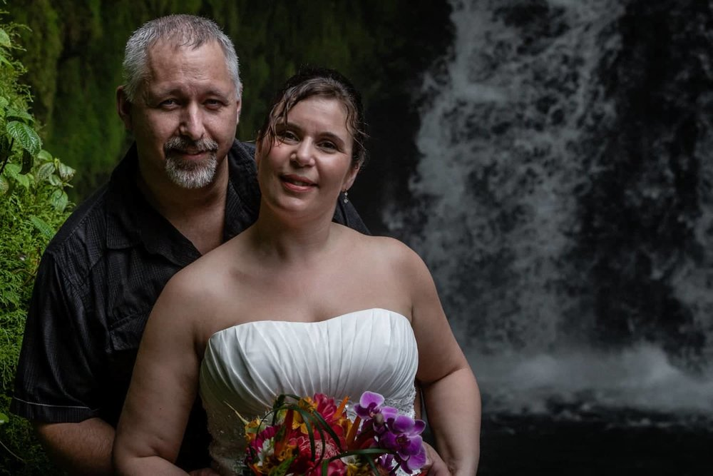 Bride and groom in front of waterfall in Costa Rica.
