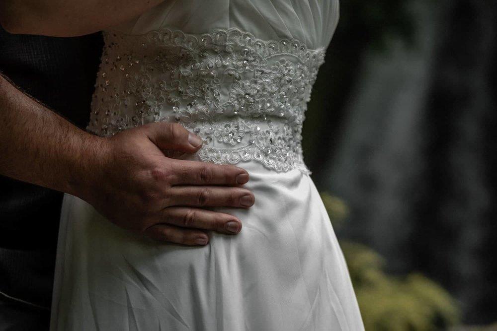 Bride wearing white wedding dress by waterfall in La Fortuna.