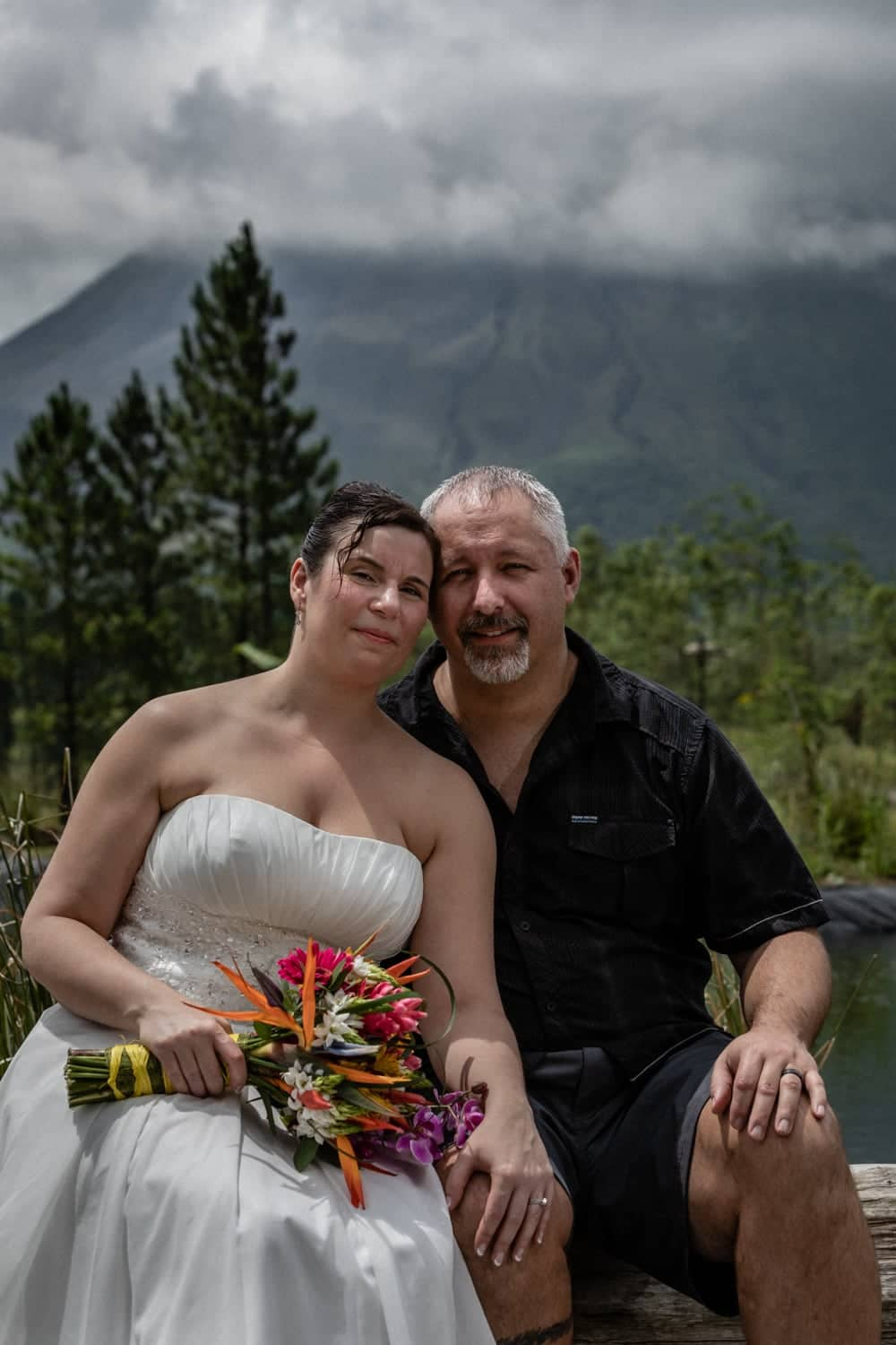 Just married couple sitting on log in front of volcano in La Fortuna.