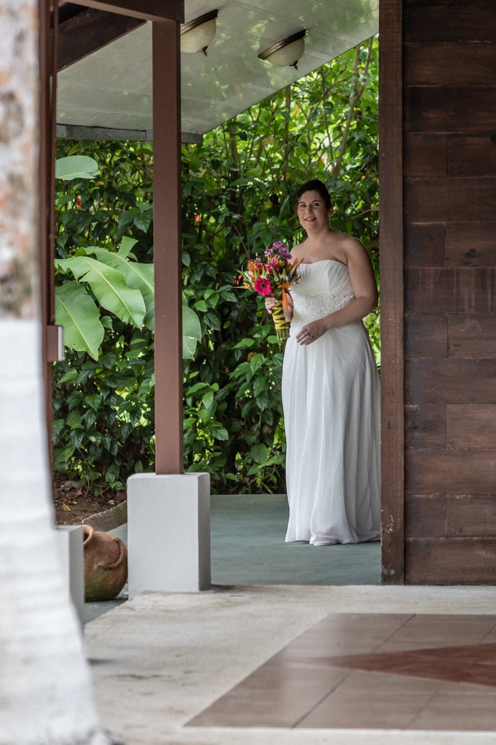 Bride with floral bouquet walks towards groom.