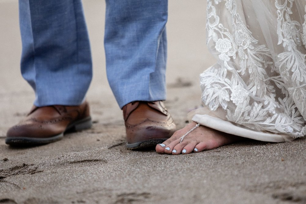 Photo of bride and groom's feet in beach sand.